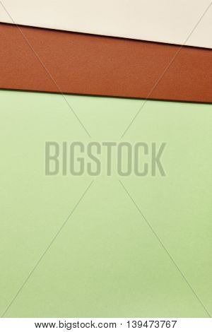 Colored cardboards background in green brown beige tone. Copy space. Vertical