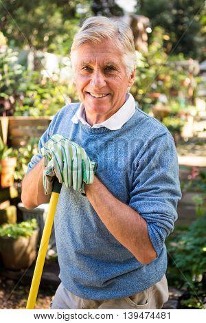 Portrait of happy mature gardener with tool at garden