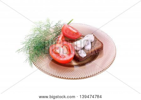 Slice of rye bread and green goods on a saucer
