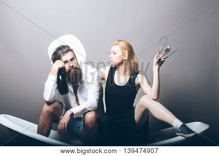 young family couple of blonde pretty girl with kitchen utensils and bearded man with long beard holding wine bottle sitting on bathtub on grey background. household everyday life and routine