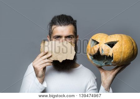 young bearded man with serious face holding brown paper sheet and orange scary halloween pumpkin in studio on grey background copy space