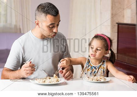 Little Girl And Father Are Having Meal Together