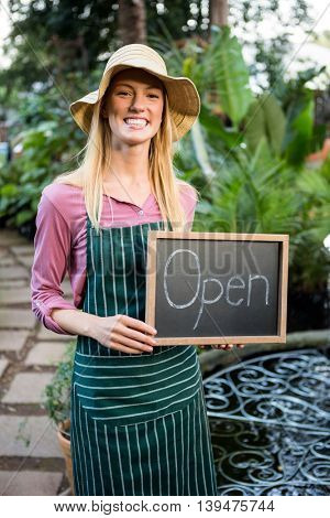 Portrait of beautiful young female gardener with open text on chalkboard at garden