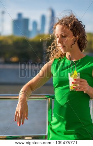 Young woman in green stands with cocktail on ship deck during sailing in city