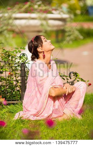 Middle age woman in pink sari and Indian adornment sunbathes on grass in summer park