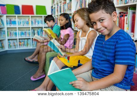 Elementary students reading books while sitting at library in school