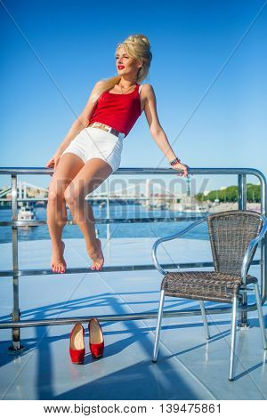 Beautiful blonde woman sits on railing at deck of ship at river in summer city
