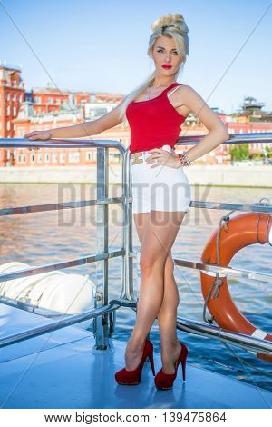 Blonde cute woman in red top on deck of ship at river near quay at summer