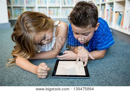 Girl and boy lying while using digital tablet at library in school