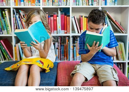 Students reading books while sitting on seats in school library