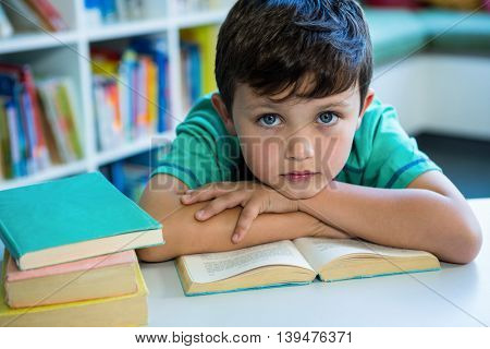 Portrait of elementary boy with book at table in school library