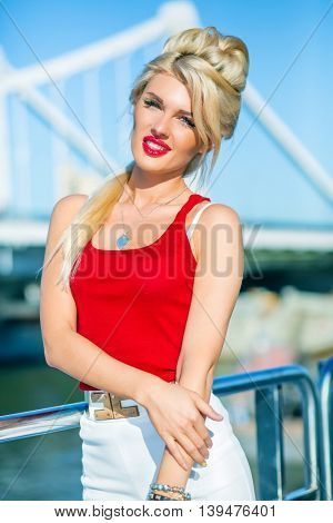 Beautiful blonde woman poses on deck of ship at river in summer city