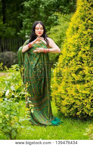 Brunette young woman in sari and Indian adornment poses near to green bush in park