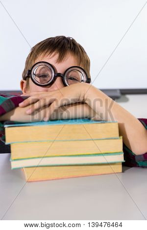 Portrait of boy leaning on books at table in classroom