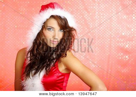 Portrait of beautiful  woman wearing sexy santa claus clothes on red background