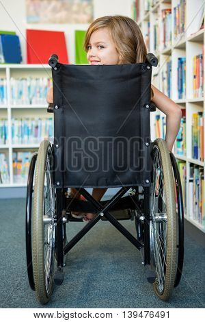 Rear view of handicapped girl on wheelchair at school library