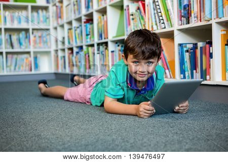 Portrait of boy using digital tablet while lying in school library