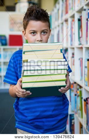 Elementary boy holding books in school library