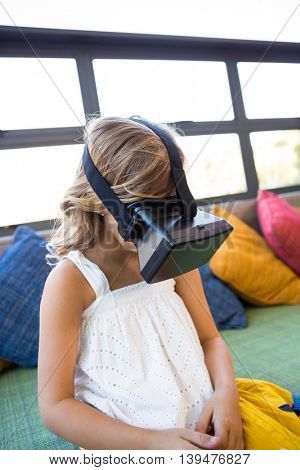 Girl using virtual reality headset while sitting on couch in school library