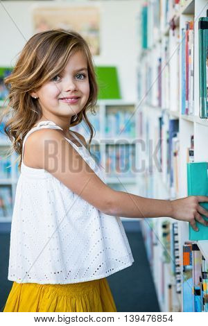 Portrait of happy girl searching books in school library