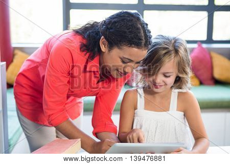 Young teacher assisting girl using digital tablet in school library