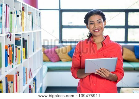 Portrait of young teacher using digital tablet at library in school