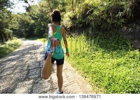 young woman trail runner warm up on country road