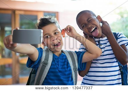 Playful classmates taking selfie at school