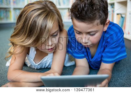 Close-up of girl and boy using digital tablet at library in school