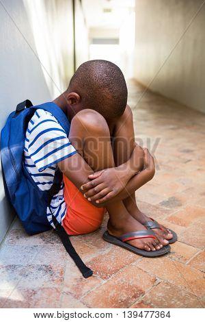 Sad boy sitting alone on corridor in school