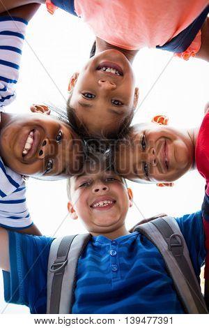 Portrait of smiling children forming huddle against sky