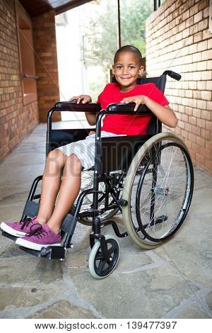 Portrait of smiling handicapped boy at school corridor