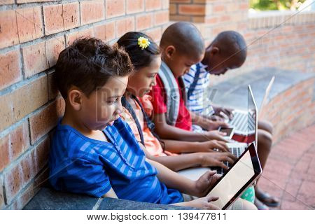Students using digital tablet and laptop while sitting at school corridor