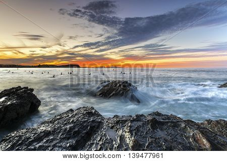 Colourful sunset with waves lashing up against a large rock in the ocean at Currumbin Rock Gold Coast