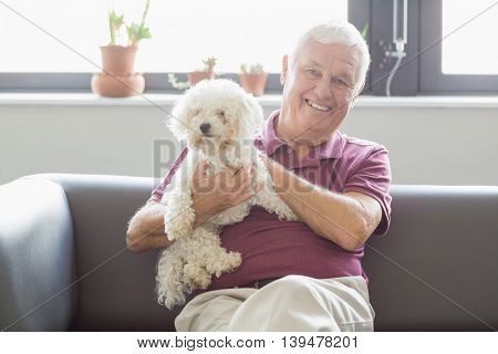 Senior man holding a dog in a retirement home