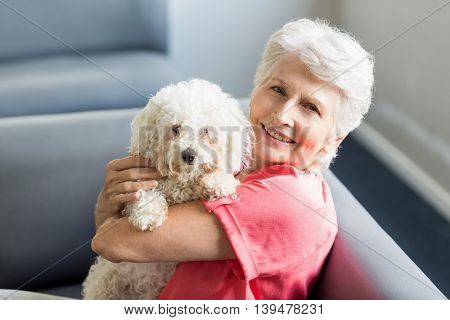 Senior woman holding a dog in a retirement home