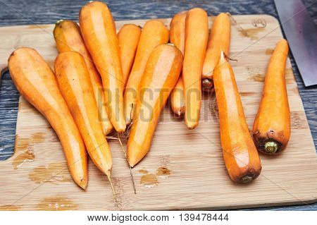 Fresh purified Carrots on Wood board. Knife near it. Wood background.