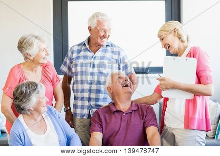 Seniors and nurse laughing together in a retirement home