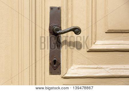Old and used door handle on a wooden door