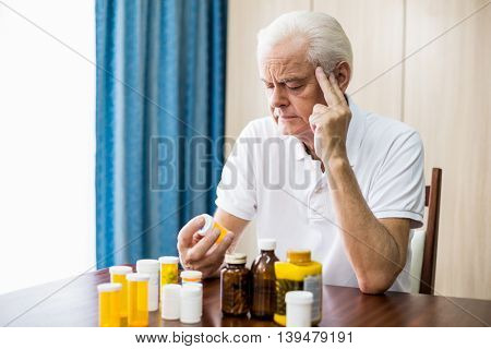 Senior sitting in front of medicine in a retirement home