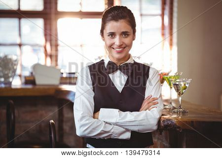 Portrait of female bartender standing with arms crossed
