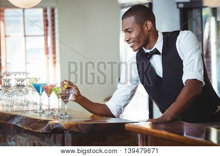 Bartender garnishing cocktail with olive on bar counter in bar
