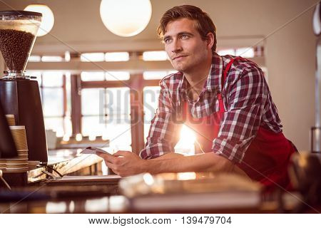 Thoughtful waiter standing with notepad at counter