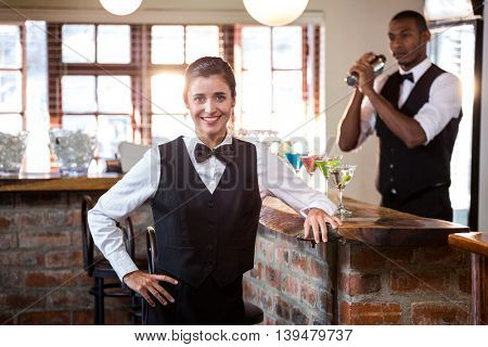 Portrait of female bartender standing at bar counter