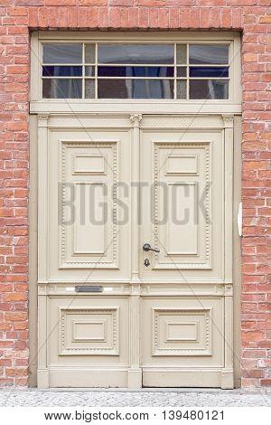 Old wooden door of a brick house