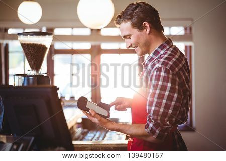 Smiling waiter standing at counter using credit card machine