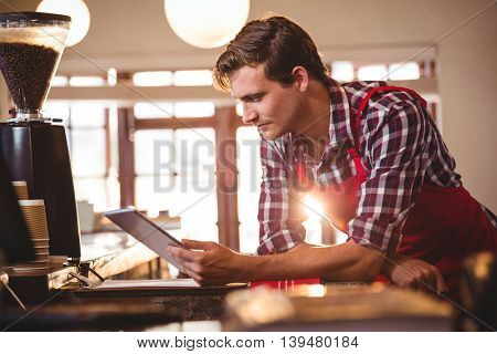 Waiter standing at counter using digital tablet