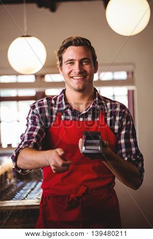 Portrait of smiling, waiter showing credit card machine at cafe