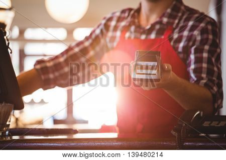 Mid section of waiter showing credit card machine at cafe