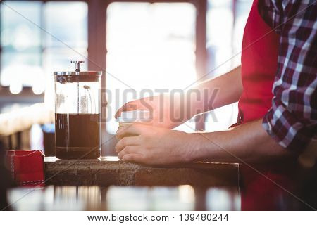 Mid section of waiter preparing coffee at cafe counter